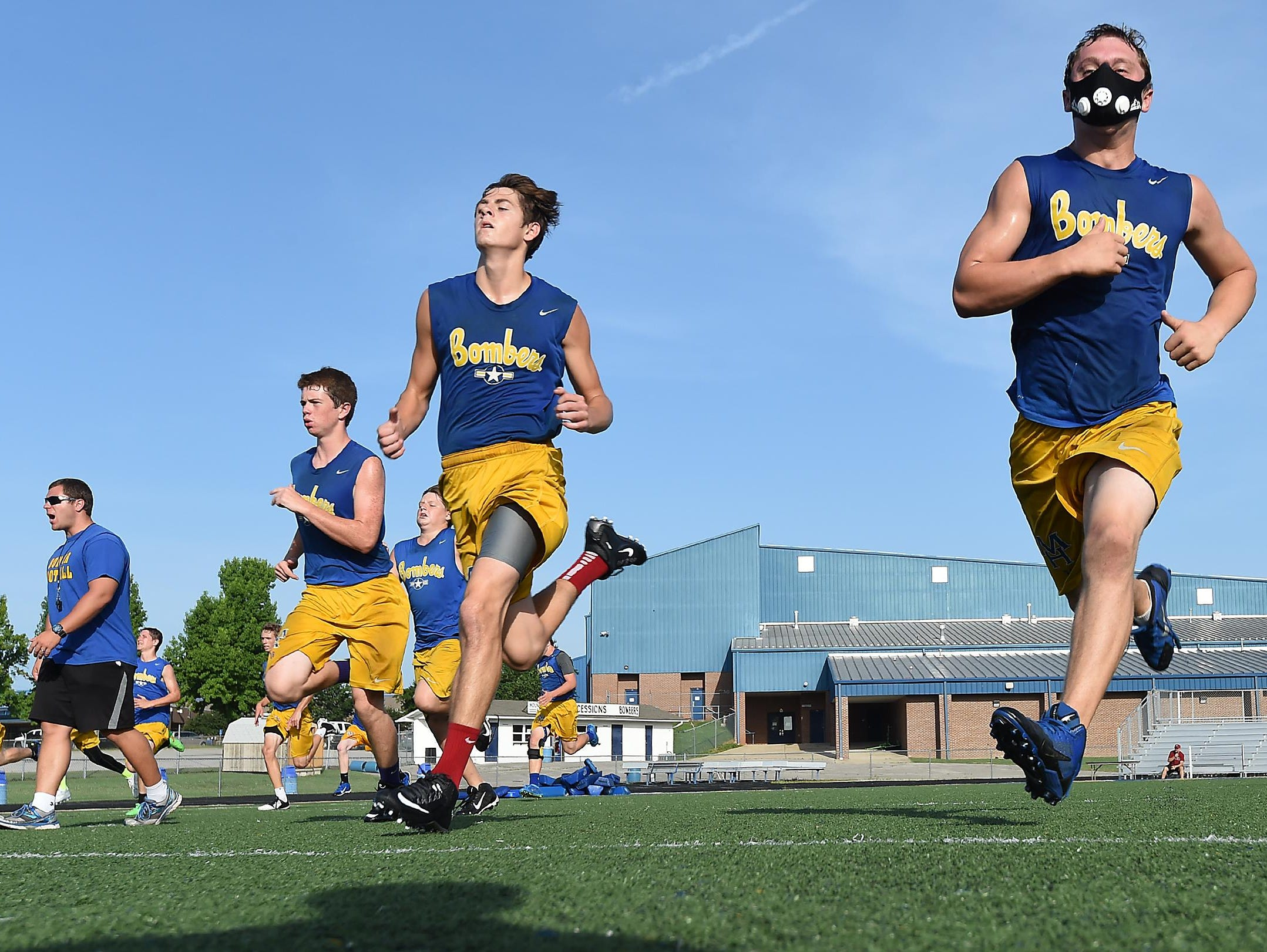 Bomber football players Riley Peters, right, and Peyton Hughes run a sprint drill Tuesday. The team is practicing several times a week this summer on a voluntary basis.