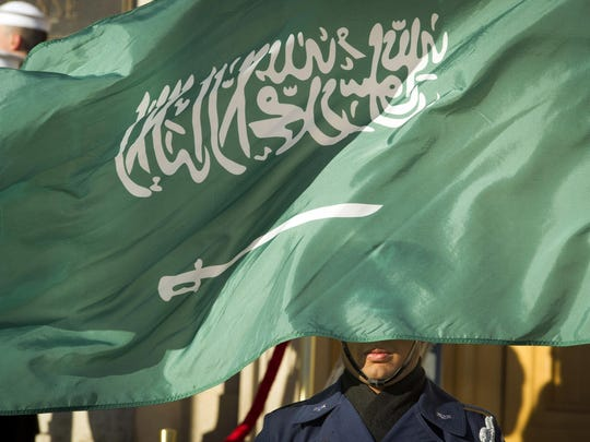 In this March 22, 2018 file photo, an Honor Guard member is covered by the flag of Saudi Arabia.