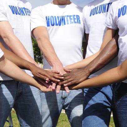 multi-ethnic volunteer group hands together
