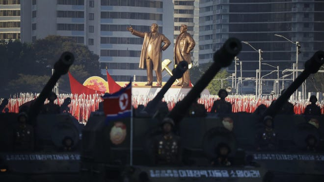In this Saturday, Oct. 10, 2015, photo, giant bronze statues of the late North Korean leaders Kim Il Sung, and Kim Jong Il, are seen towering over military soldiers with their missiles and rockets as they parade through the Kim Il Sung Square in Pyongyang, North Korea during the 70th anniversary celebrations of its ruling party's creation. (AP Photo/Wong Maye-E)