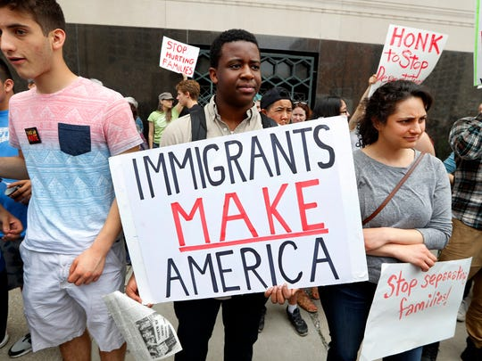 In this May 16 file photo, Torianto Johnson, a freshman at Pioneer High School in Ann Arbor, Mich., holds a sign supporting immigrants during a rally outside a federal courthouse in Detroit.