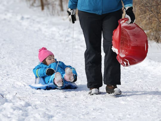 Charlotte Tran kicks back and enjoys the sled ride with her mom Erika,right, Sunday afternoon as they walk to the big hill in Southeastway Regional Park,