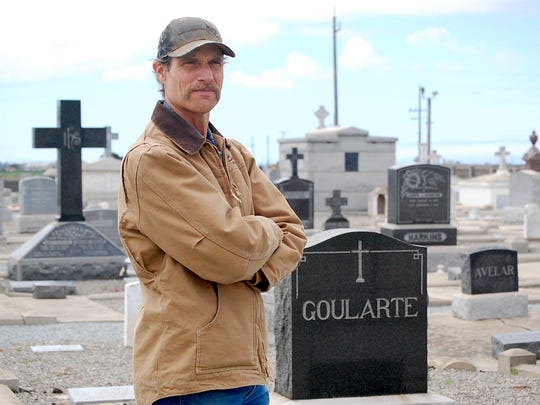Old Calvary Cemetery Restoration Committee Chair Wayne Gularte stands near a relative's headstone bearing the name Goularte spelled slightly differently.