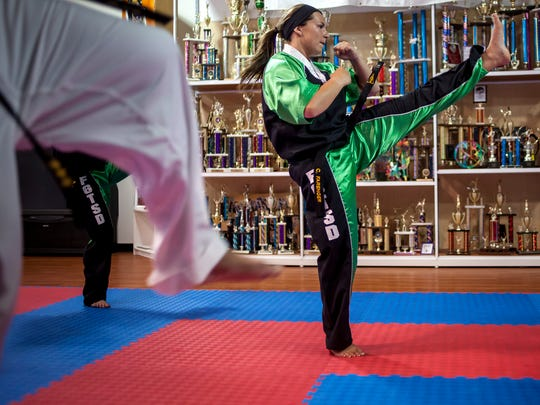 Caitlyn Farenger, 19, practices a form along with other Fort Gratiot Tang Soo Do members during a training session Wednesday, June 28, 2016 at Kaleidoscope Gym in Kimball Township.