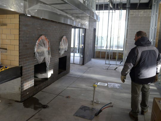 Hinterland Brewing Co. owner Bill Tressler inspects two of the wood-fired ovens at his new Titletown District restaurant Friday.