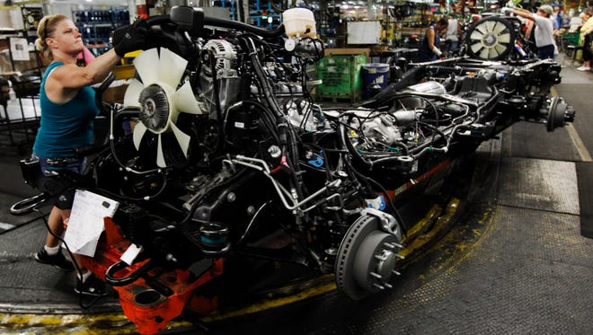 A worker assembles a pickup truck at the General Motors Flint assembly plant in Flint, Mich., in this 2011 file photo.