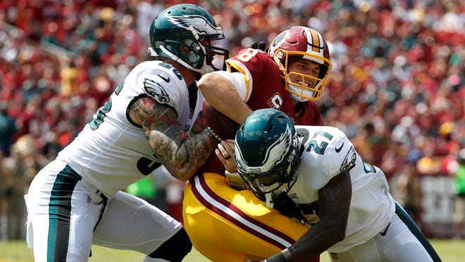 Washington Redskins quarterback Kirk Cousins, center, is tackled by Philadelphia Eagles defensive end Chris Long, left, and strong safety Malcolm Jenkins as he rushes the ball in the first half of an NFL football game, Sunday, Sept. 10, 2017, in Landover, Md.