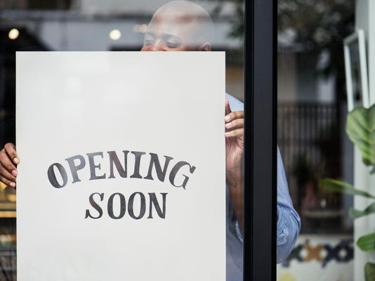 Man putting on store opening soon sign