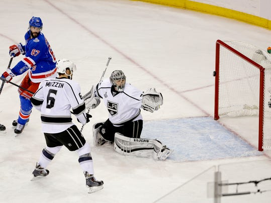 New York Rangers left wing Benoit Pouliot (67) redirects the puck past Los Angeles Kings goalie Jonathan Quick (32) for a goal as Los Angeles Kings defenseman Jake Muzzin (6) looks on in the first period during Game 4 of the NHL hockey Stanley Cup Final, Wednesday, June 11, 2014, in New York. (AP Photo/Frank Franklin II)