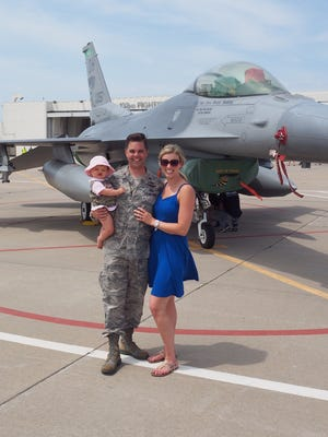 Maj. Zach Nunn, Kelly Nunn and daughter Olympia Nunn stand with an F-16 at the Des Moines International Airport.