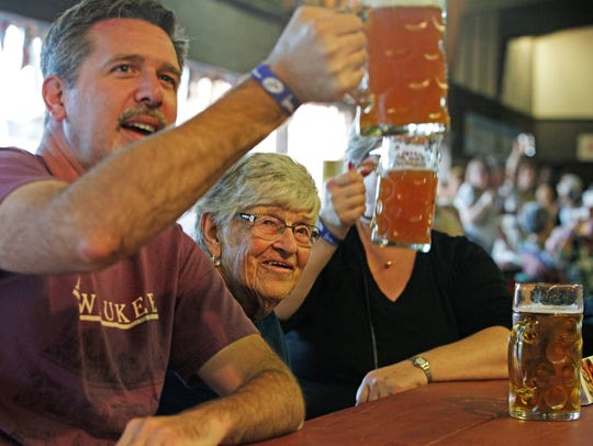 Paul Sherwood raises a stein of beer and sings along with his mother-in-law, Helen Pup, at Oktoberfest in Glendale in 2014. This year's event kicks off Friday, Sept. 7.