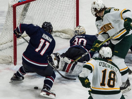 UConn goalie Adam Huska looks to the net along with UVM's Brian Bowen after a near score during their Hockey East men's hockey match up at Gutterson Fieldhouse Tuesday night, Nov. 21, 2017.
