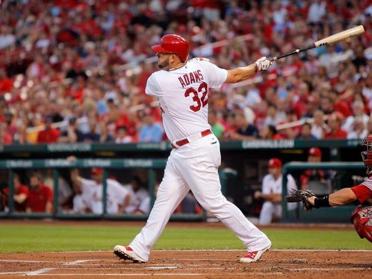 St. Louis Cardinals' Matt Adams hits an RBI double during the first inning of a baseball game against the Cincinnati Reds, Monday, Aug. 18, 2014, in St. Louis. (AP Photo/Scott Kane)