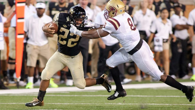 Sep 3, 2015; Winston-Salem, NC, USA; Wake Forest Demon Deacons running back Matt Colburn (22) gets grabbed by the face mask by Elon Phoenix defensive back Chris Blair (8) during the fourth quarter at BB&T Field. Wake Forest defeated Elon 41-3. Mandatory Credit: Jeremy Brevard-USA TODAY Sports