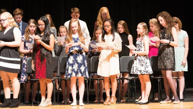 Some new members of Lakeside Middle School's National Junior Honor Society take the pledge during the induction ceremony on March 28.