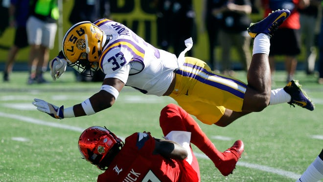 Louisville wide receiver James Quick is stopped by LSU safety Jamal Adams (33) after a reception Dec. 31, 2016, in Orlando.