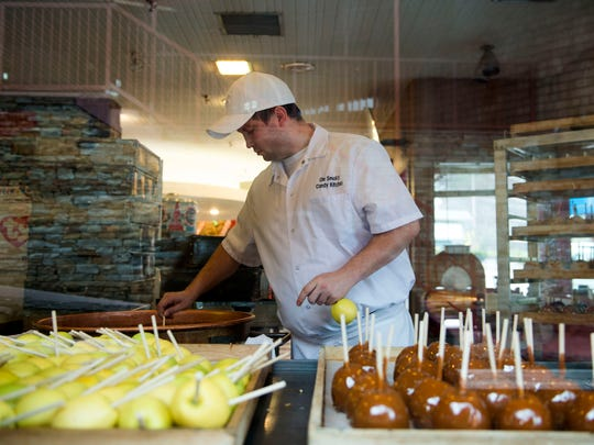 Jacob Smith dips caramel apples at Ole Smoky Candy