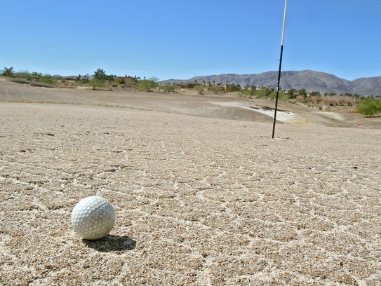 A golf ball sits on a green that hasn't been watered