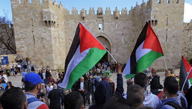 Palestinians carry national flags during a protest marking Land Day in front of the Damascus Gate in Jerusalem's Old City, on Monday, March 30, 2015. Land Day commemorates riots on March 30, 1976, when six people were killed during a protest by Israeli Arabs whose property was annexed in northern Israel to expand Jewish communities.