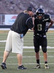 Desert Hills coach Carl Franke talks with quarterback