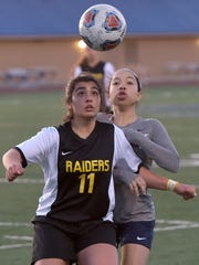 Raider Natalie George (11) and Falcon Kristina Agee (2) play heads-up soccer in Thursday's city championship game.