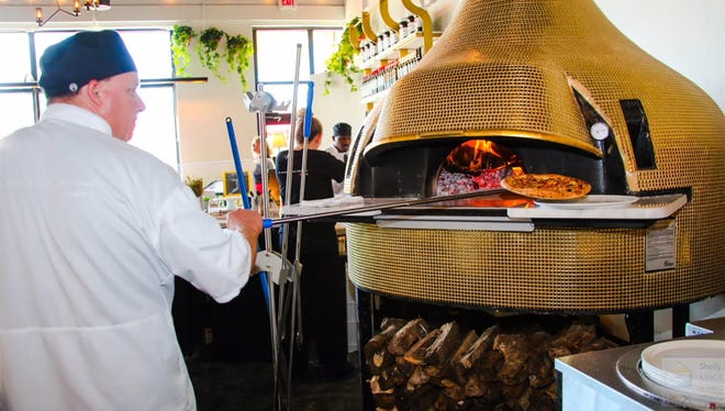 Pizzas are baked in wood-fired ovens in a centralized, open kitchen at the new MidiCi: The Neapolitan Pizza Co. at Coconut Point in Estero.