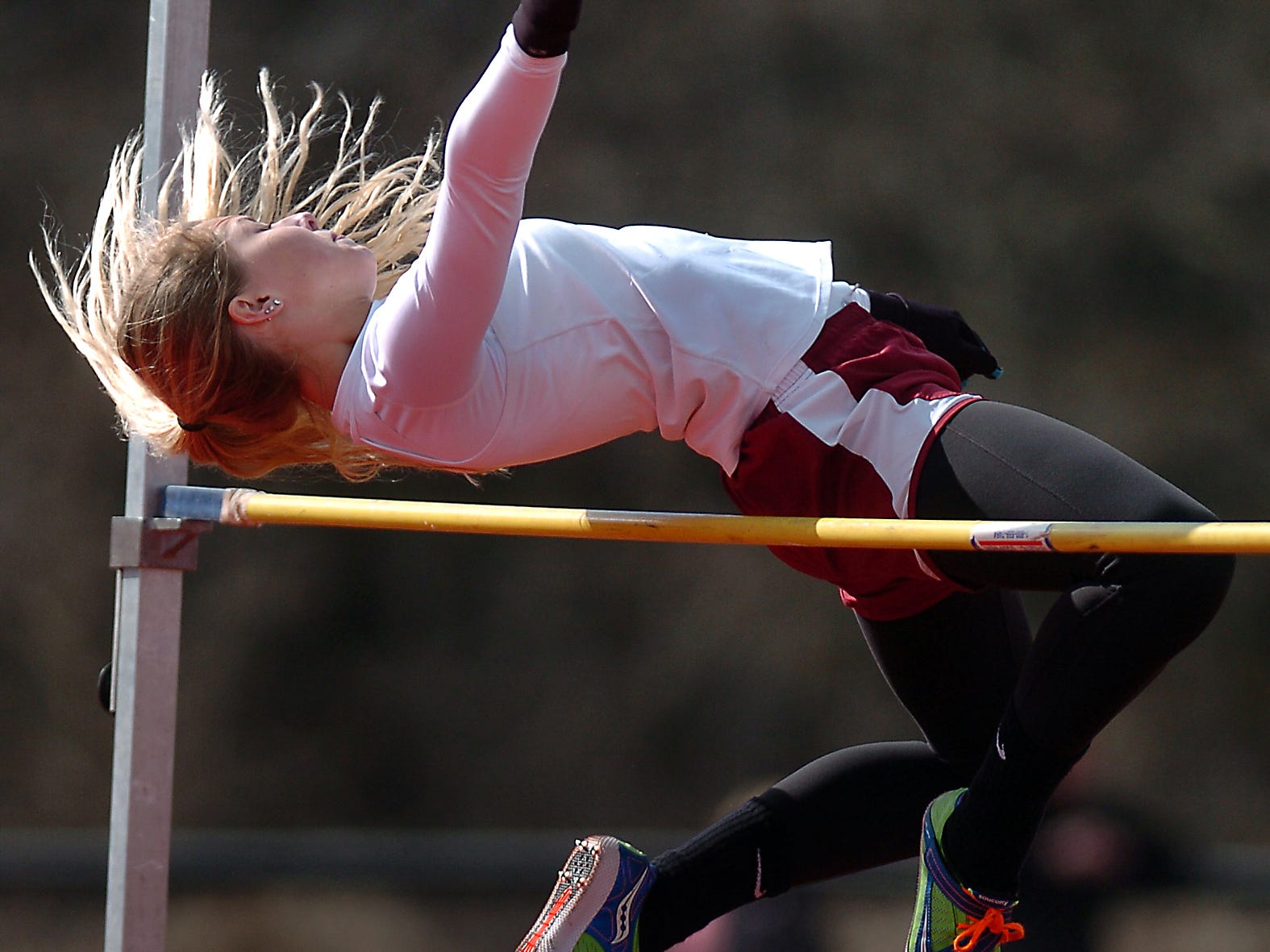 Milford's Whitney Mergens clears the bar in the high jump against Brighton.