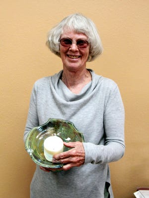 Pamela Page poses with the winning chalice design from among the six designs she created for the Unitarian Universalist Fellowship of Silver City. For the past several weeks fellowship members have voted for their favorite. The flaming chalice is a primary symbol of the Unitarian Universalist faith tradition. UUs have many different interpretations of the flaming chalice, including the light of reason, the warmth of community, and the flame of hope.