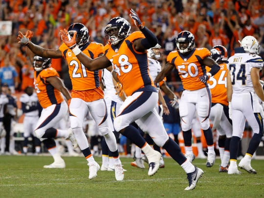 Denver Broncos outside linebacker Shaquil Barrett (48), cornerback Aqib Talib (21) and inside linebacker Zaire Anderson (50) run off the field with one second left on the clock in an NFL football game against the Los Angeles Chargers after a blocked field goal attempt, Monday, Sept. 11, 2017, in Denver. The Broncos won 24-21. (AP Photo/Jack Dempsey)