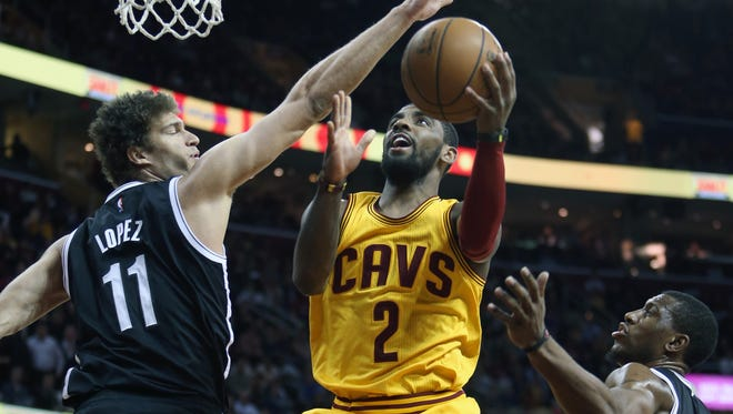 Kyrie Irving scores between Nets center Brook Lopez and forward Thaddeus Young at Quicken Loans Arena.