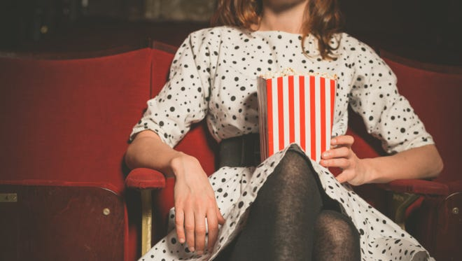 Young woman sitting in movie theater with popcorn