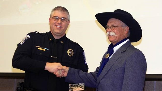 Monett Police Department chief, left, awards Animal Control Officer Glenn Palade.