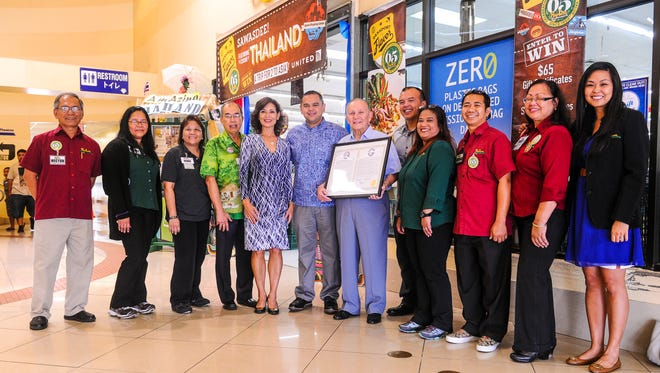 Paul Calvo, Pay-Less Supermarkets Inc. president, displays a legislative resolution presented by Sen. Dennis Rodriguez Jr., center, as he and Pay-Less management pose for a photo at the entrance of the Agana store on July 7. The company was recognized by the Guam Legislature for the celebration of its 65th anniversary of doing business on island. From left: Dededo Store Manager Hector De Leon, Sinajana Store Manager Stacey Quitugua, Micronesia Mall Store Manager Bernie Onedera, Agana Store Manager Bob Field, Executive Vice President Kathy Sgro, Sen. Rodriguez, Calvo, General Manager Mike Benito, Oka Store Manager Pepita Conteras, Yigo Store Manager Ramon Imbat, Sumay Store Manager Doris De Guzman and Marketing Manager Carina Pegarido.