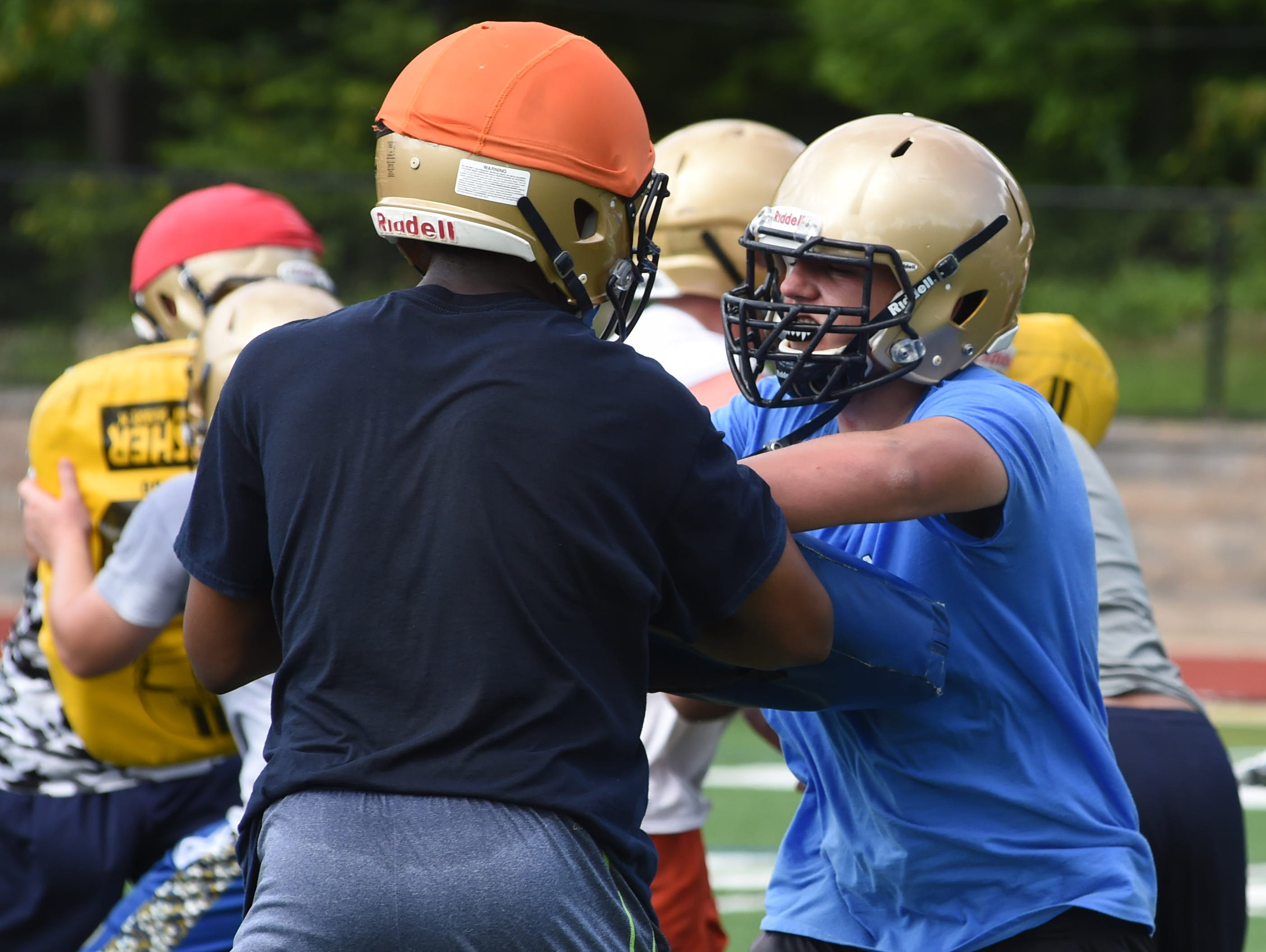 Juniors Malik Wright, left, and Dan Napolitano, right, of Our Lady of Lourdes High School grapple during preseason football practice.