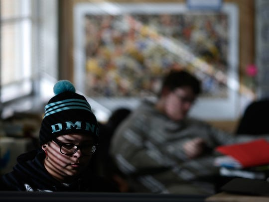 Kevin Lopez works at his desk  during class at the