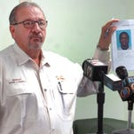 St. Landry Parish Sheriff Bobby Guidroz holds up a mug shot of Harrison Lee Riley during a press conference Friday to announce the charges related to the shooting and stabbing incident Wednesday in Sunset.