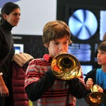 """Jack Herlihy, 10, plays with a horn at the grand opening of the Fort Collins Museum of Discovery. The museum is hosting """"Geek Week"""" during spring break."""