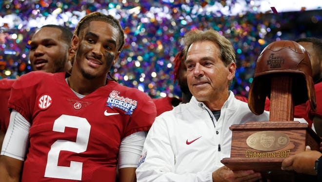 Alabama quarterback Jalen Hurts and Alabama head coach Nick Saban stand with the Leather Helmet trophy after their game against Florida State in Atlanta.