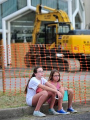 Addy Williams, 13, left, and her sister Bella, 11, wait to see a demolition of an entrance of Bellevue Center in Bellevue on Saturday, Aug. 22, 2015. This is the first step to making One Bellevue Place on the property.