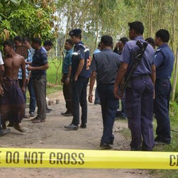 Bangladeshi security officers stand by the site where a Japanese Kunio Hoshi was killed at Mahiganj village in Rangpur district, 300 kilometers (185 miles) north of Dhaka, Bangladesh, Saturday, Oct. 3, 2015.