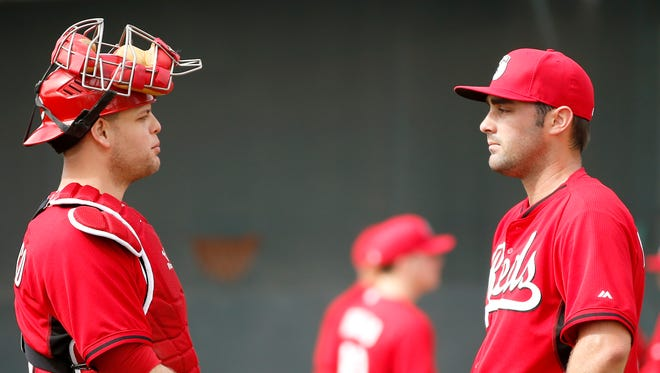 Reds catcher Devin Mesoraco talks with pitcher Matt Magill during pitching drills Feb. 22, 2015 in Goodyear.