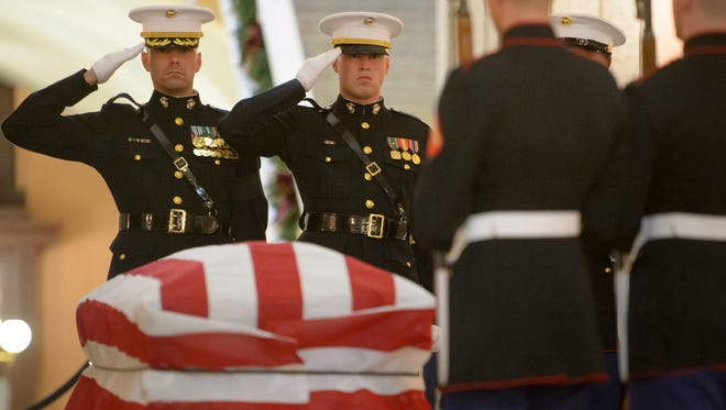 In this photo provided by NASA, the United States Marine honor guard performs a Changing of the Guard as former astronaut and U.S. Senator John Glenn lies in repose, in the Rotunda of the Ohio Statehouse in Columbus, Ohio, Friday, Dec. 16, 2016.  (Bill Ingalls/NASA via AP)