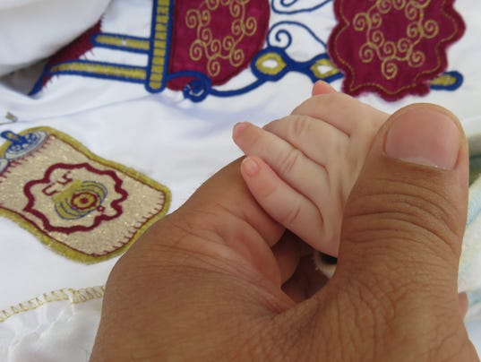 boy holding his father's hand during circumcision