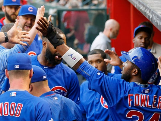 Chicago Cubs' Dexter Fowler, right, celebrates his run against the Arizona Diamondbacks during the fourth inning of a baseball game Saturday, April 9, 2016, in Phoenix. (AP Photo/Ross D. Franklin)