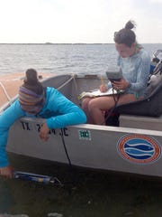 Christina Bonsell and Meaghan Cuddy, both grad students at UT Marine Science Institute, gather data, such as salinity, temperature and turbidity in the water column of a bay within the Mission-Aransas National Estuarine Research Reserve.
