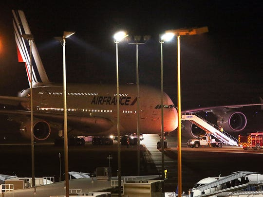 Emergency vehicles sit parked near an Air France plane