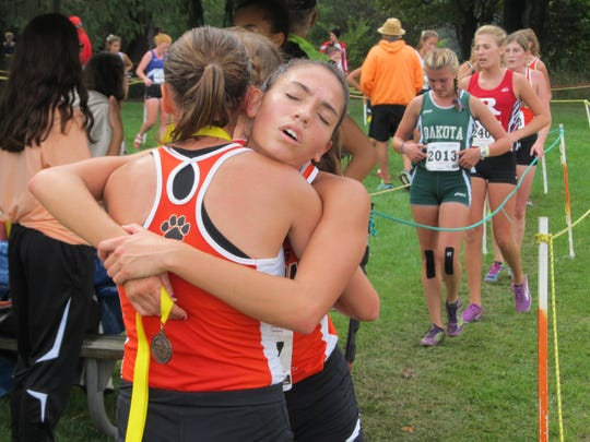 Lexi Reynolds (right) hugs Brighton cross country teammate