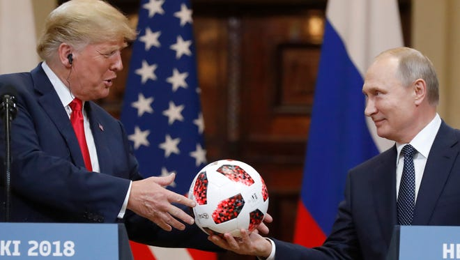 Russian President Vladimir Putin gives a soccer ball to President Donald Trump, left, during a press conference after their meeting at the Presidential Palace in Helsinki, Finland, July 16, 2018.