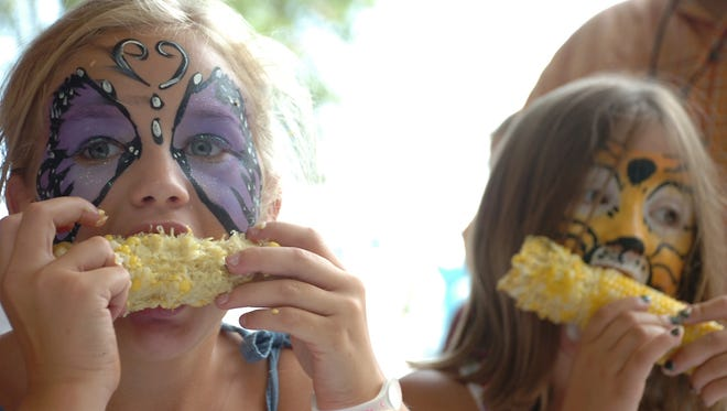 Cambrie Jeansonne (left) and Callie Ducote, both of Cottonport, compete in a corn eating contest at the Corn Festival in Bunkie.