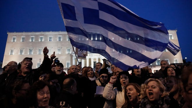 Pro-government protesters wave Greek flags in front of Greece's parliament to support the newly elected government's push for a better deal on Greece's debt, in central Athens on Feb. 15, 2015.